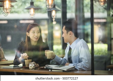 Asian business man and woman meeting in a coffee shop.