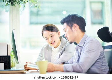 asian business man and woman working together in office using tablet PC.