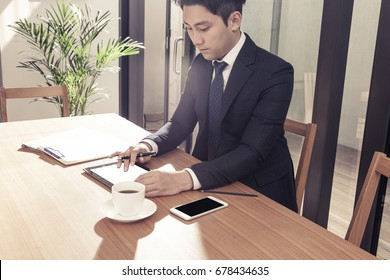 An asian business man work with tablet, smart phone, coffee on the wood desk.