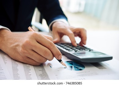 asian business man working with hand pointing graph discussion and analysis data charts and graphs and using a calculator to calculate  numbers.Business finances and accounting concept