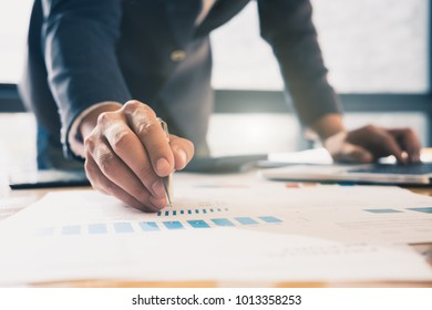 asian business man working with new startup project hand pointing graph discussion and analysis data charts and graphs.Business finances and accounting concept