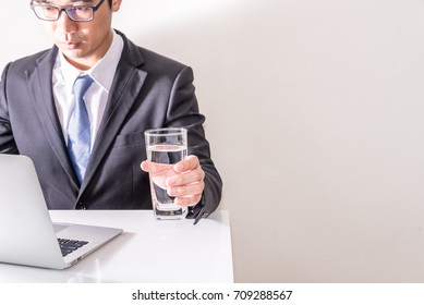 Asian business man working online and hold glass of water in the office, Man in suit and necktie type notebook on table, free space at right side on white background.