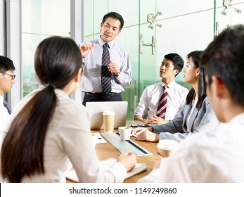 asian business manager talking to team during meeting in modern office.