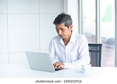 Asian Business old man with white hair and shirt and laptop is working, thinking, planning in the meeting room at the modern office about the future of the company how to get success and avoid failure