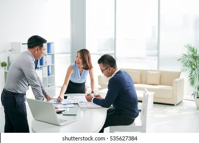 Asian business partners working with papers in the office