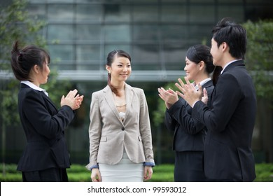 Asian business people applauding a colleague. Image depicting success and achievement.
