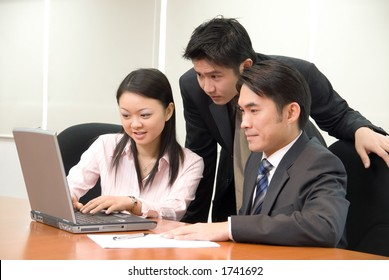 Asian business people in business attire working on a notebook pc