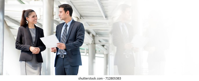Asian business people discussing document while walking outdoors - panoramic banner with copy space