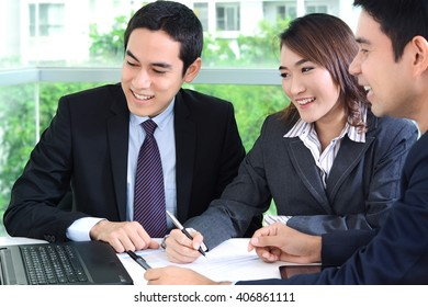 Asian business people discussing and smiling in a meeting
