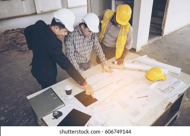 Asian business people group on meeting and presentation in construction site with construction engineer architect and worker looking building model and blueprint plan blueprint plans