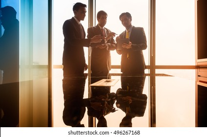 Asian business people having conversation in front of window in conference room, filtered image