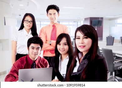 Asian business people with laptop posing together in a modern office