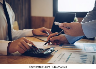 Asian business people meeting with new startup project pointing graph discussion and analysis data charts and graphs.Business finances and accounting concept