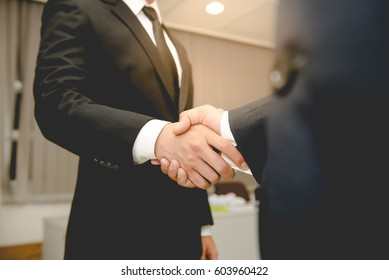 Asian Business people shaking hands, finishing up a meeting,mission complete