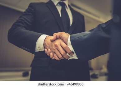 Asian Business people shaking hands, finishing up a meeting,mission complete,Two business people are holding hands to business cooperation in a future