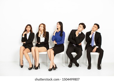 asian business people sitting on the chairs in a row