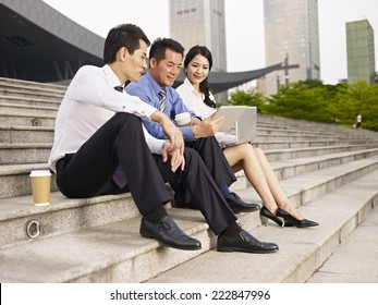 asian business people sitting on steps and looking at tablet computer.