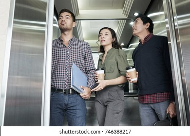 Asian business people with take-out coffee in elevator
