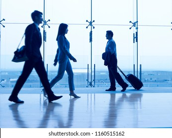 asian business people walking in airport terminal building, focus on the background.