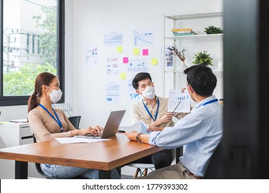 Asian business people wear face mask working and meeting in office to protect infection of coronavirus covid-19, reopen business with new normal and social distancing concept