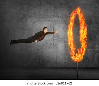 Asian business person flying through ring of fire. Business risk conceptual