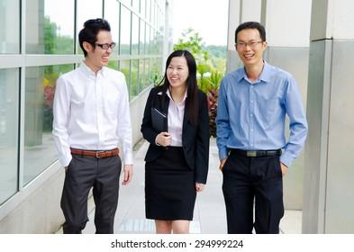 Asian business team having conversation while walking