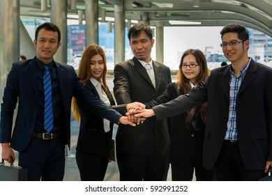 Asian Business Team showing Unity with their hands together as Business Teamwork Concept