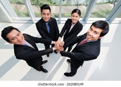 Asian business team stacking their hands, view from above