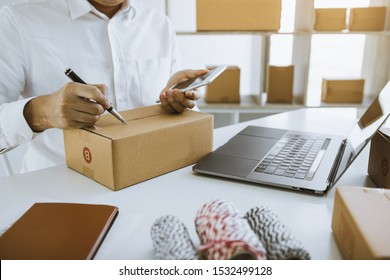 Asian business teenager is looking on tablet and writing a customer address contact to deliver the package to the customer at the destination.
