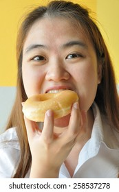 Asian business woman 28 years old in uniform eating plain donut. junk food.