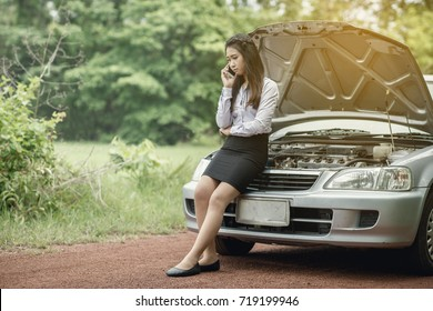 Asian business woman calling for help with the mobile phone with beautiful hair and broken down car in country