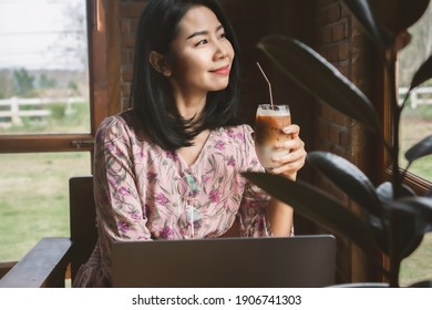 Asian business woman drinking coffee and working on computer laptop at cafe shop,  work from anywhere concept