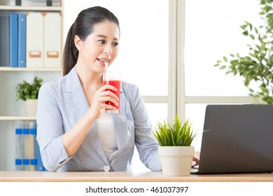 asian business woman drinking watermelon juice and use computer for business