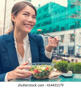 Asian business woman eating healthy salad vegetarian takeaway cafe meal at work during lunch break on outdoor terrace city park in summer. Happy businesswoman having a balanced diet for weight loss.