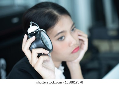 Asian business woman feeling tired and bored waiting for someone coming late at work and looking at alarm clock, waiting time concept.