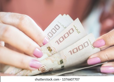 Asian business woman hand  counting money Thai baht paper currency , can be used for saving ,debt,payment concept background