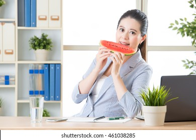 asian business woman happy to biting fresh watermelon fruit