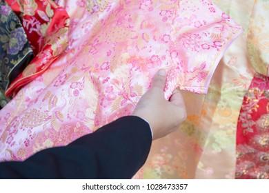 Asian business woman hold pink color qipao dress at Yaowarat, Bangkok, Thailand