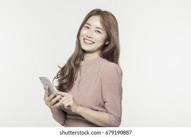 An asian business woman holding a smart phone isolated white.