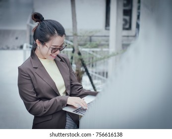 Asian business woman with laptop happy and smile concept success work