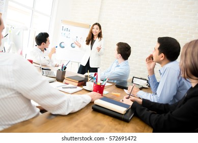 Asian business woman leader presenting work to mixed race colleagues in the meeting