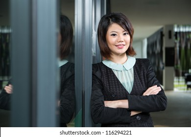 Asian Business woman leaning against a window.