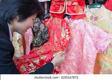 Asian business woman look at red qipao dress at Yaowarat, Bangkok, Thailand