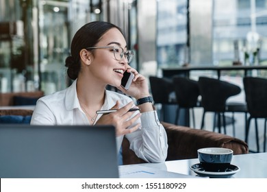 Asian business woman making a phone call and smiling indoor