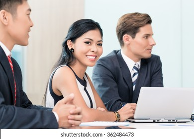 Asian Business woman in meeting looking at camera