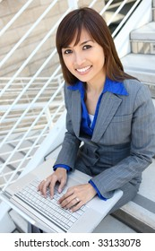 An asian business woman on stairs at office with laptop computer