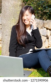 Asian business woman in park working with pc and phone smiling looking camera