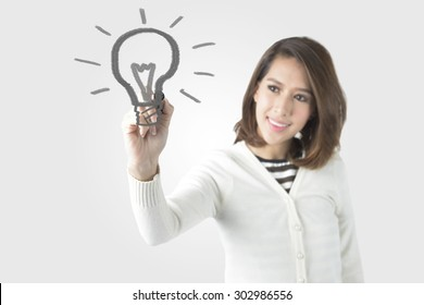Asian Business Woman With Pen Drawing Light Bulb. Concept for New Ideas