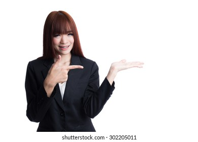 Asian Business woman pointing to empty palm hand, presenting, gesturing, isolated on white background