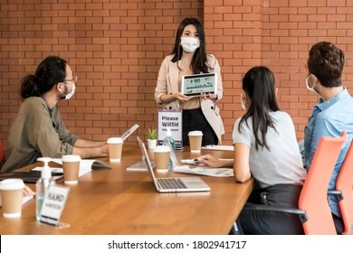 Asian business woman present her work in meeting for brainstorm. They wear protective face mask in new normal office preventing coronavirus COVID-19 spreading.
